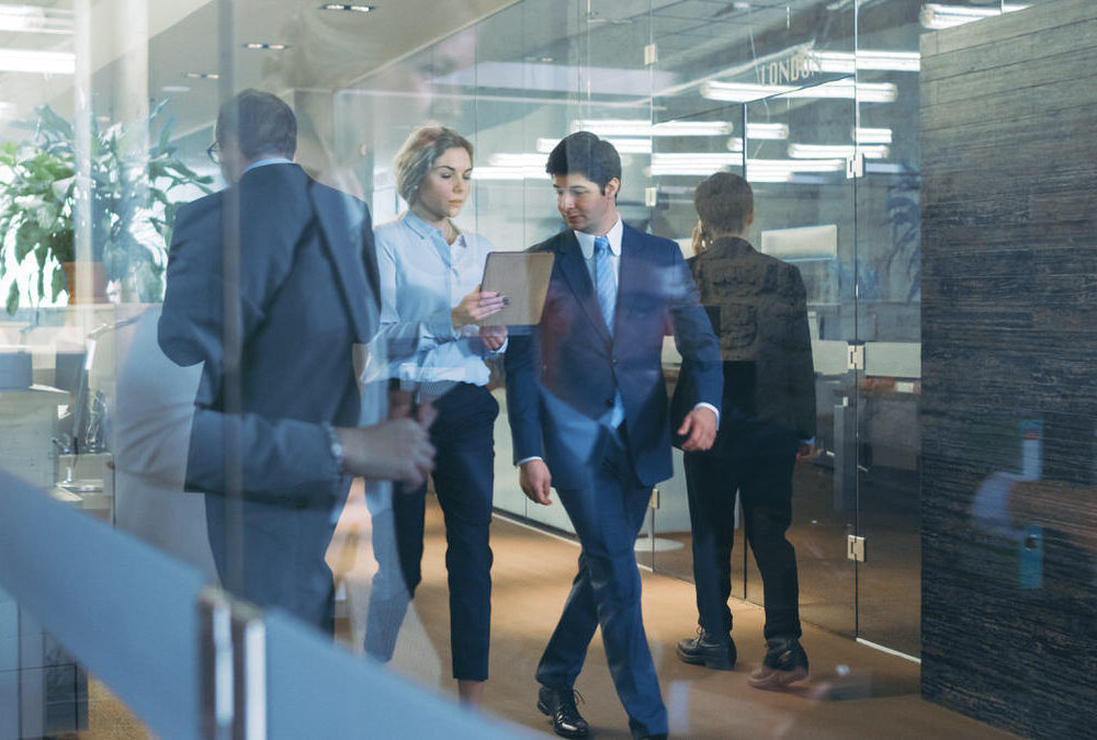 Businessman,And,Businesswoman,Walking,Through,Glass,Hallway,,Discussing,Work,And
