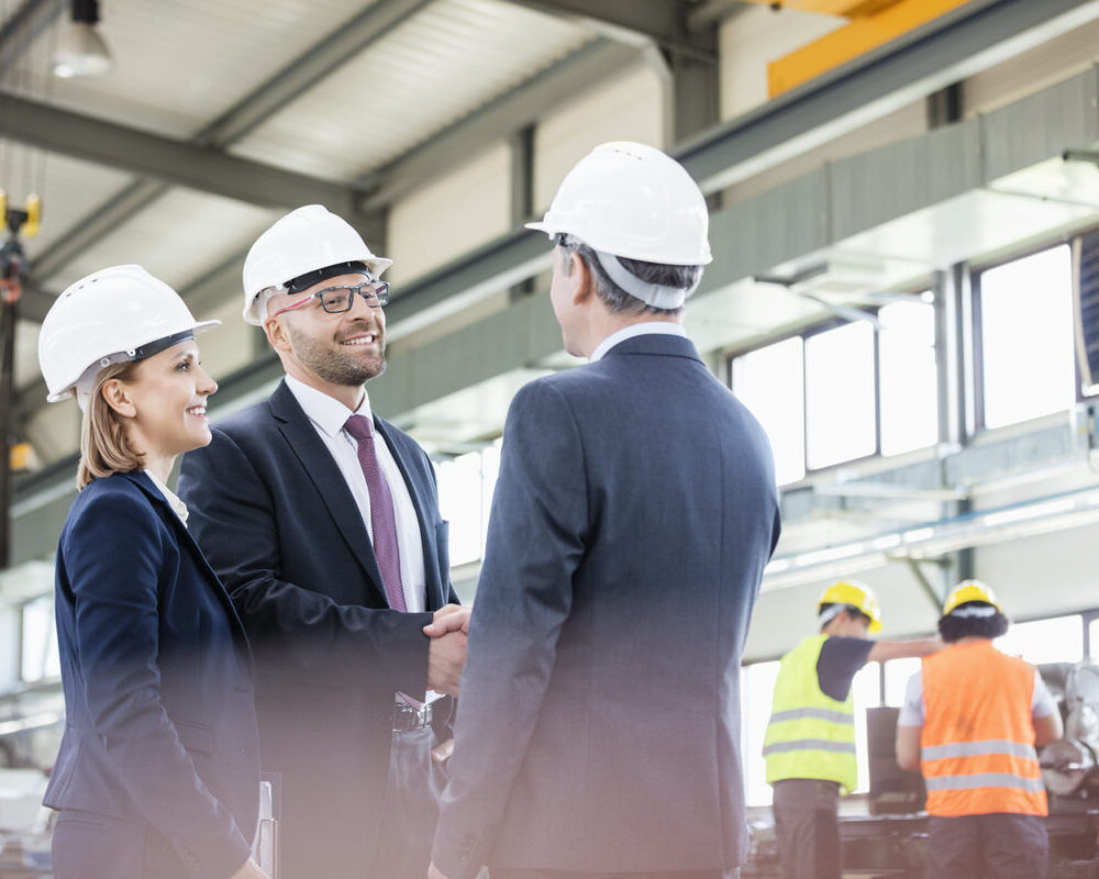 Businessmen,Shaking,Hands,With,Workers,Working,In,Background,At,Metal