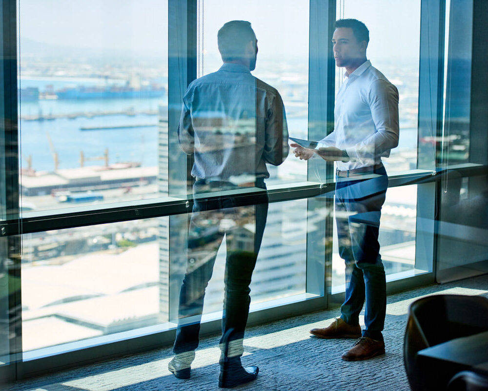 Two,Businessmen,Deep,In,Discussion,Together,While,Standing,By,Windows