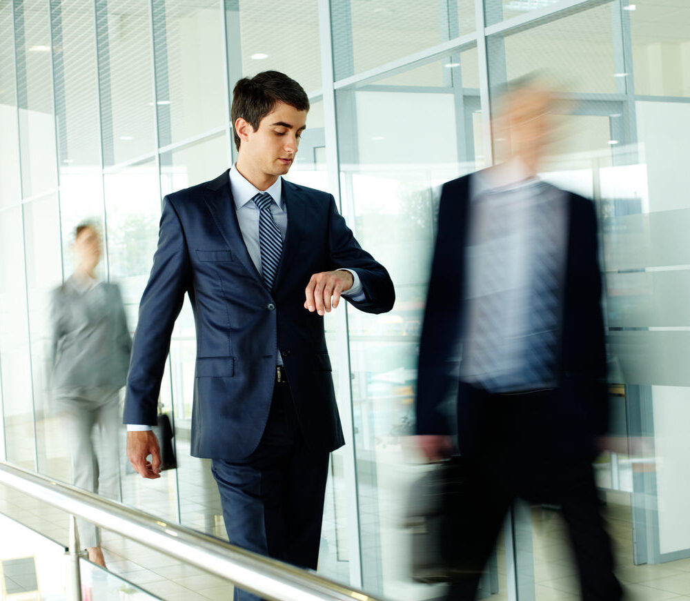Businessman,Looking,At,Watch,With,Walking,People,On,Background