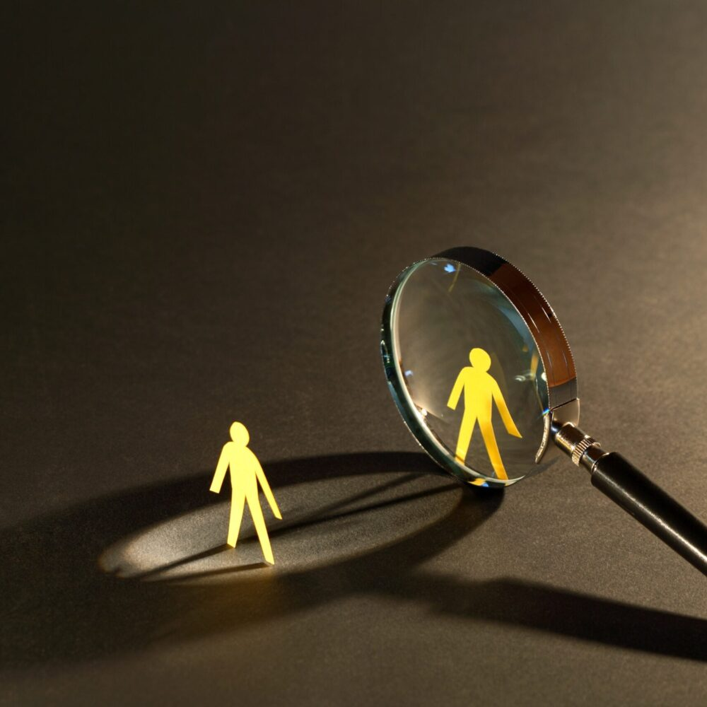 11157209 - magnifying glass standing between two small paper men on dark surface